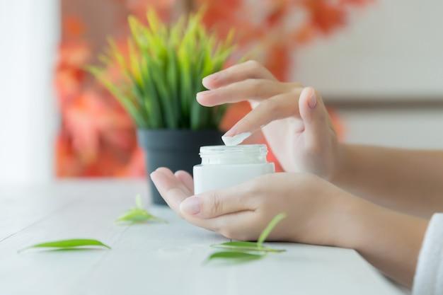 Mulher segura um frasco com um creme cosmético nas mãos dela