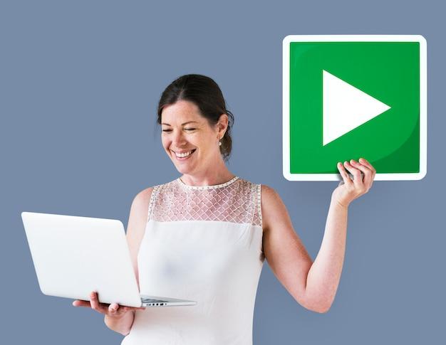 Mulher segura, um, jogue botão, e, um, laptop