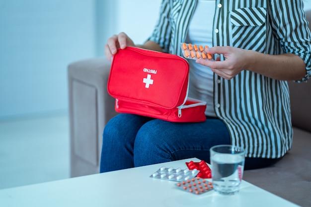 Mulher segura um kit médico com medicamento em casa. primeiros socorros para dor e doença
