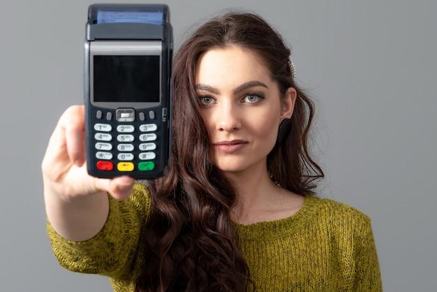 Mulher segura um moderno terminal de pagamento bancário para processar a aquisição de pagamentos com cartão de crédito