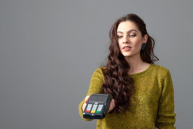 Mulher segura um moderno terminal de pagamento bancário para processar pagamentos de aquisição com cartão de crédito