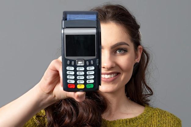 Mulher segura um moderno terminal de pagamento bancário para processar pagamentos de aquisição de cartão de crédito, conceito de estilo de vida