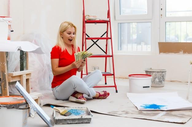 Mulher segura um pacote de dólares com instrumentos para apartamento de renovação