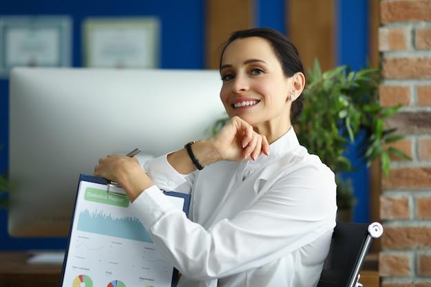 Mulher segura um relatório estatístico perto do monitor