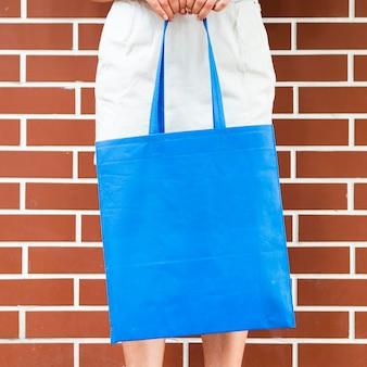 Mulher segura um saco azul