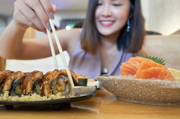 Mulher segura, um, sushi, com, chopsticks, comer