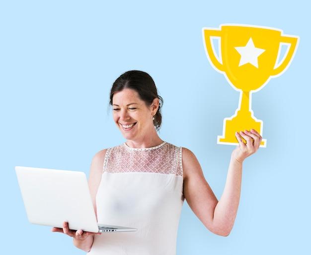 Mulher segura, um, troféu, ícone, e, usando, um, laptop