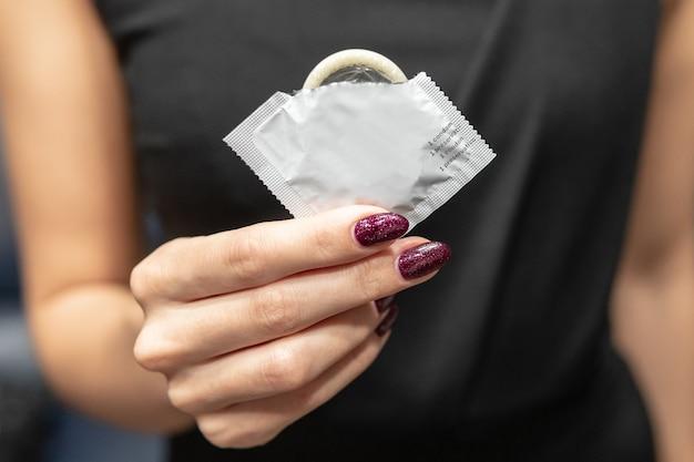 Mulher segura uma camisinha na mão. o conceito de sexo seguro