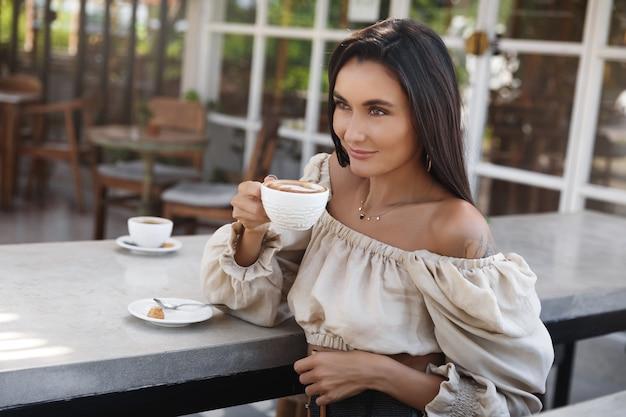 Mulher segura uma caneca com café e sorrindo.