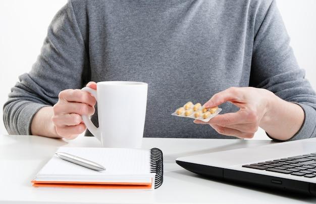 Mulher segura uma caneca e comprimidos em uma mesa com um computador. uma mulher trabalha em uma mesa em um computador.