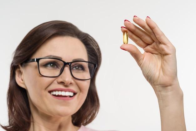Mulher segura uma cápsula com vitamina e, óleo de peixe