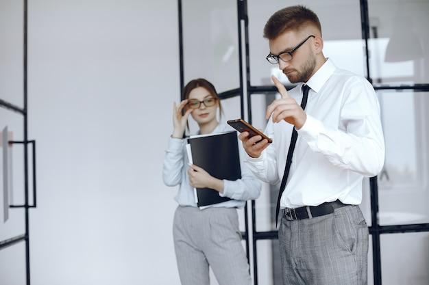 Mulher segura uma pasta. parceiros de negócios em uma reunião de negócios. o homem usa o telefone. pessoas com óculos