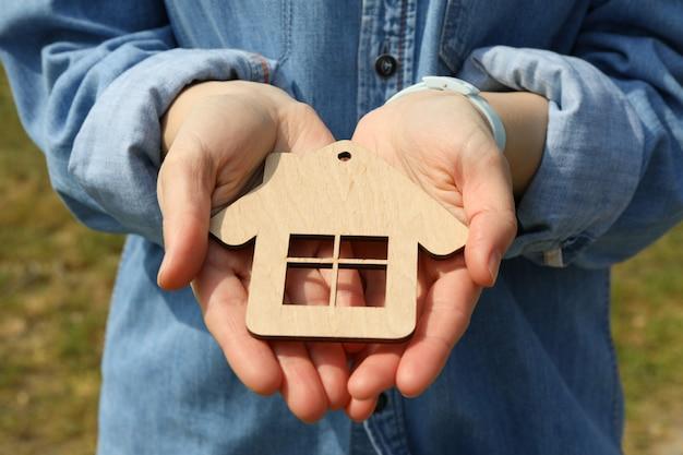 Mulher segura uma pequena casa de madeira. comprando um imóvel