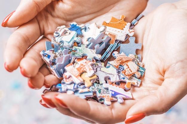 Mulher segura uma pilha de quebra-cabeças nas mãos.
