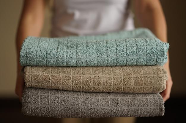 Mulher segura uma pilha de toalhas turcas neutras multicoloridas com as duas mãos