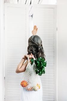 Mulher segura uma sacola com comida, frutas e legumes frescos