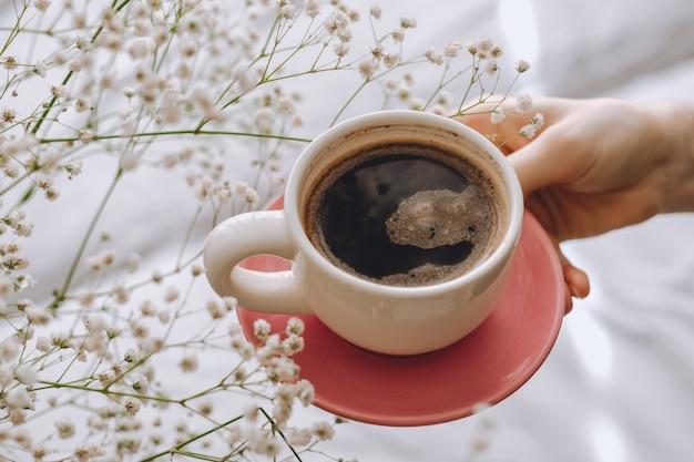 Mulher segura uma xícara de café pela manhã. fundo branco com flores de gipsófila