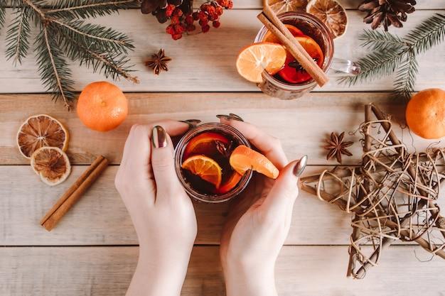 Mulher segura uma xícara de vinho quente com especiarias nas mãos. bebida de aquecimento de inverno para os feriados.