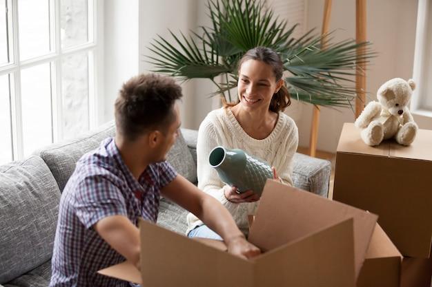 Mulher segura, vaso, ajudando, homem, caixas embalagem, ligado, dia móvel