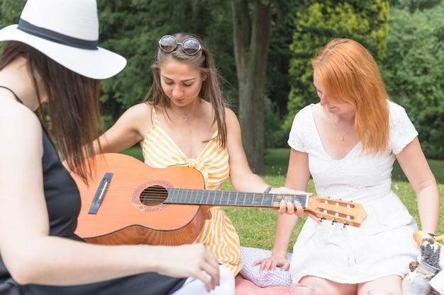 Mulher segura, violão, sentando, com, dela, amigos, parque