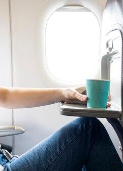 Mulher segura, xícara café, em, avião