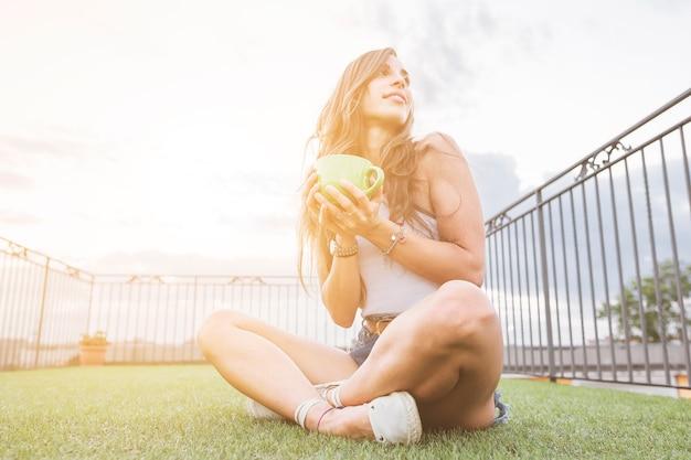 Mulher segura, xícara café, sentando, ligado, relvado verde, em, sacada