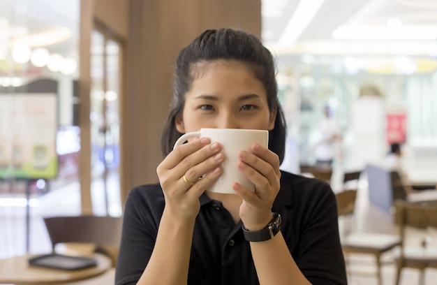 Mulher segura xícara de café no café