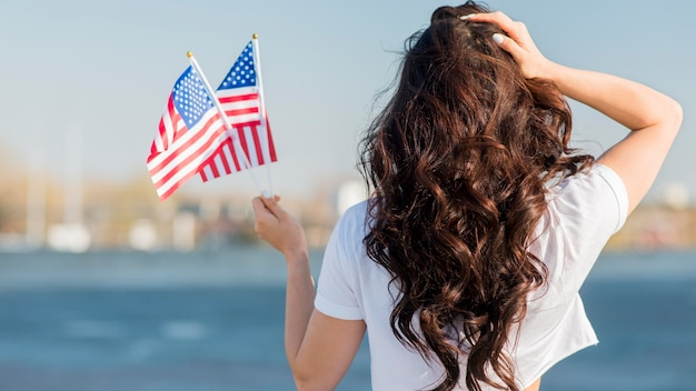 Mulher segurando 2 bandeiras dos eua por trás