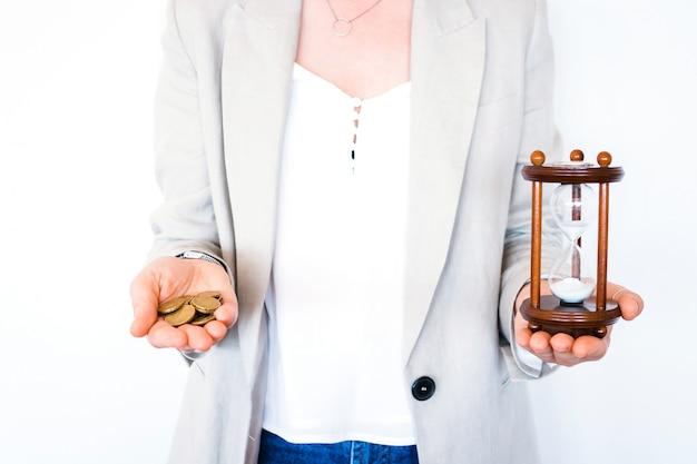 Mulher segurando a ampulheta e moedas isoladas no fundo branco. investimento de tempo e poupança de aposentadoria. temporizador de contagem regressiva de urgência para o conceito de prazo de negócios. tempo é dinheiro