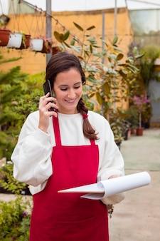 Mulher segurando a área de transferência e falando no telefone em estufa