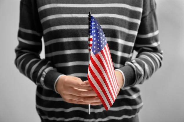 Mulher segurando a bandeira americana na luz. imigração para os eua