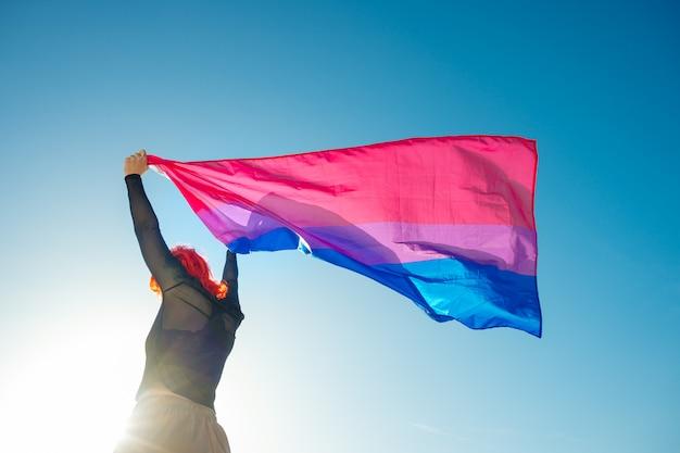Mulher segurando a bandeira bissexual do arco-íris com o céu azul
