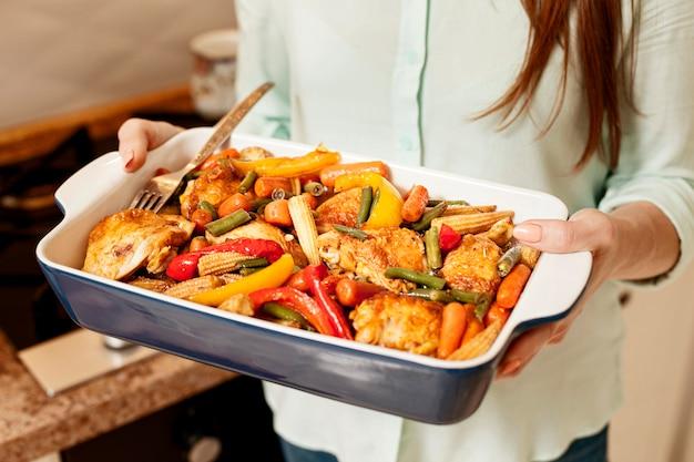 Mulher segurando a bandeja de comida para o jantar