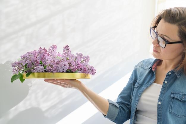 Mulher segurando a bandeja dourada com flores nas mãos para decoração de interiores