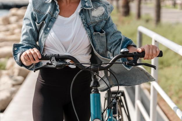 Mulher segurando a bicicleta pelo guidão