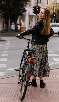 Mulher segurando a bicicleta por trás da foto