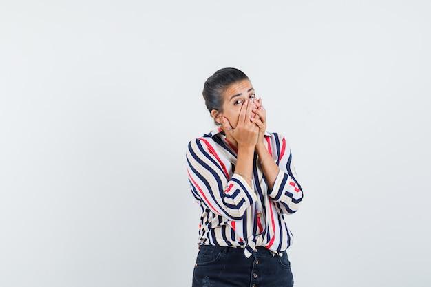 Mulher segurando a boca com as mãos na camisa, saia e parecendo chocada