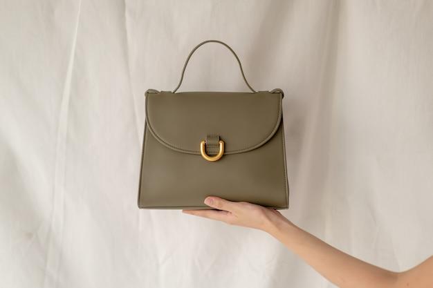 Mulher segurando a bolsa de couro