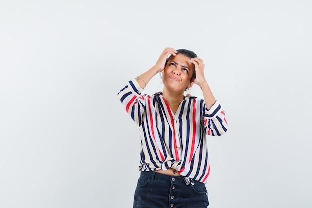 Mulher segurando a cabeça com as mãos na camisa, saia e parecendo hesitante