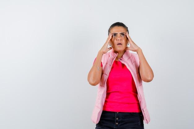 Mulher segurando a cabeça com as mãos na camiseta, colete e parecendo indefesa