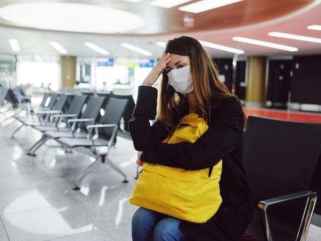 Mulher segurando a cabeça com máscara médica no aeroporto esperando o atraso do voo