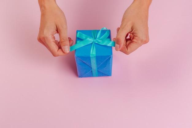 Mulher segurando a caixa de presente na cor