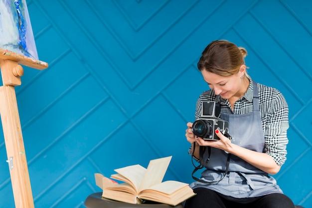 Mulher segurando a câmera e livro