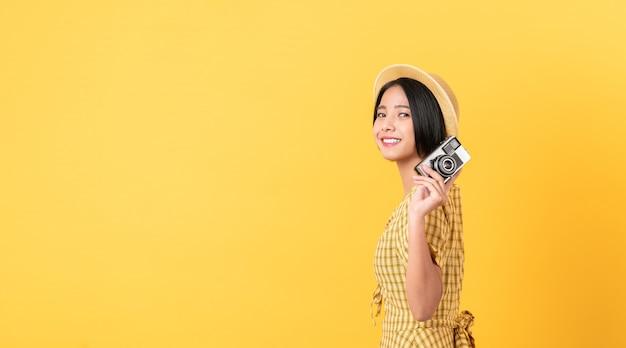 Mulher segurando a câmera em fundo amarelo