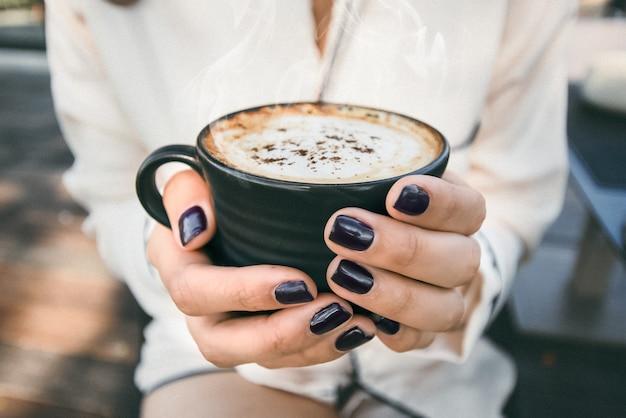 Mulher segurando a caneca de café closeup vista