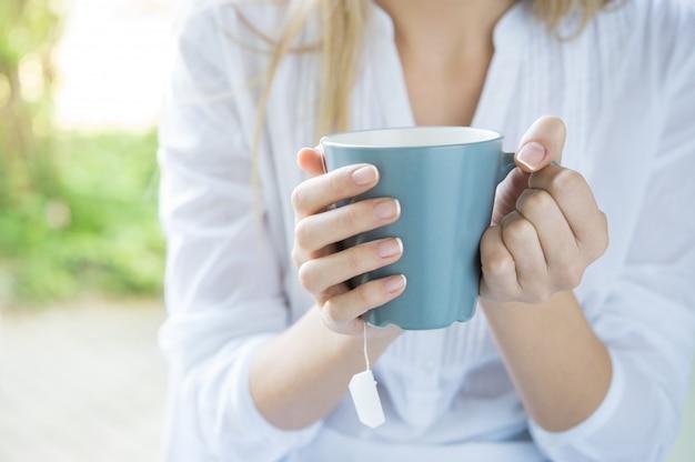 Mulher segurando a caneca de chá