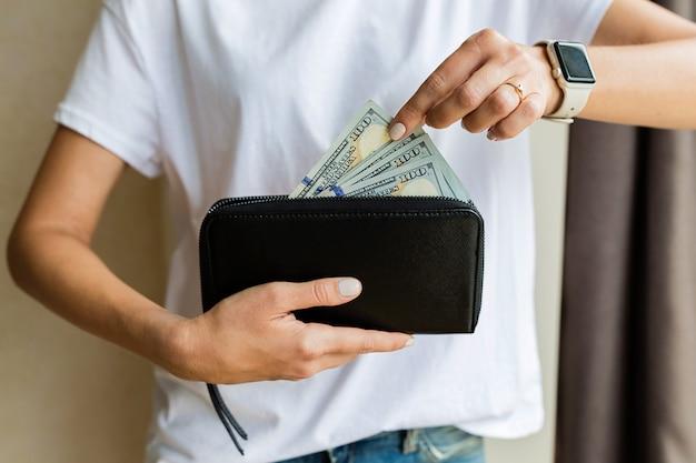 Mulher segurando a carteira de mão com dinheiro