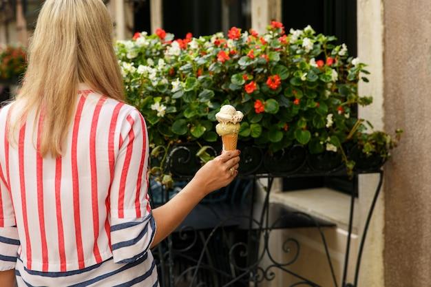 Mulher segurando a casquinha de sorvete no fundo colorido
