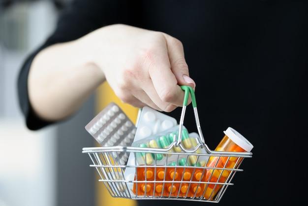 Mulher segurando a cesta de medicamentos em seu close da mão. conceito de polifarmácia