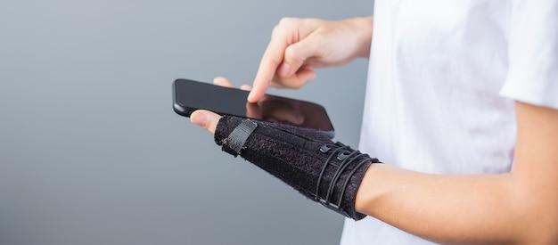 Mulher segurando a dor no pulso porque usa o smartphone há muito tempo. conceito de tenossinovite, sintoma de interseção, síndrome do túnel do carpo ou síndrome de escritório de de quervain